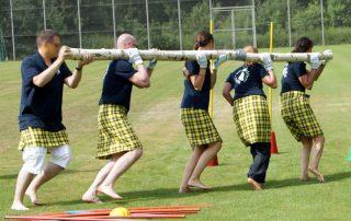 Highland Games: Team trägt Baumstamm durch Hindernissparcours
