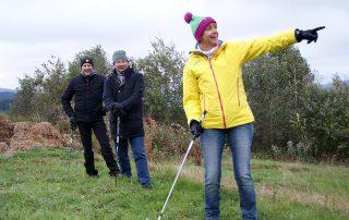 Crossgolfen Teamevent - Das Team steht am Abschlag, Frau zeigt auf Ziel